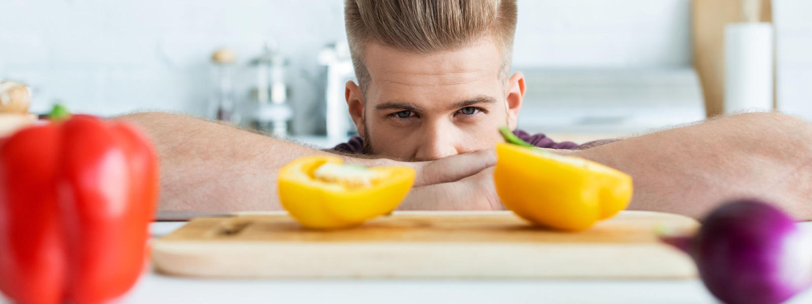 Photo of male person looking at halves of yellow bell pepper